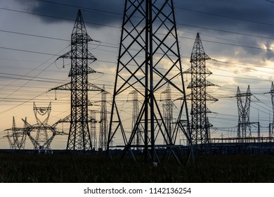 Electricity transmission pylon silhouetted against sunset sky. High voltage electric tower line.