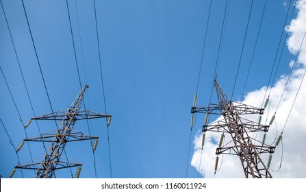 Electricity transmission pylon silhouetted against blue sky at dusk
