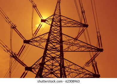 electricity transmission pylon silhouetted against sun