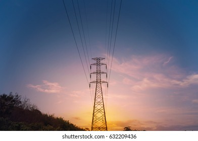 electricity transmission pylon silhouetted against blue sky at sunset