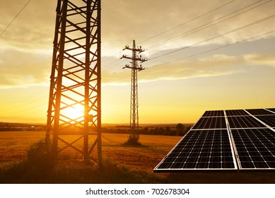 Electricity transmission pylon with solar panel on field against the sunset.