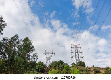 Electricity transmission towers against blue sky background. Horizontal color photography.