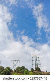 Electricity transmission towers against blue sky background. Vertical color photography.