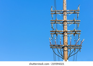 Electricity wood utility pole with copy space. Front view of electrical power high voltage distribution lines showing insulators and connections. Blue sky background.