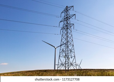 Electricty pylon with power lines erected in front of a wind turbine with a blue sky background. Renewable energy concept.