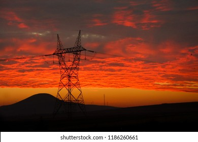 Electricty transfer lines and a pylon during sunrise in a dramatic scene