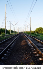 Electrified double-track railway at sunset. Double railroad tracks