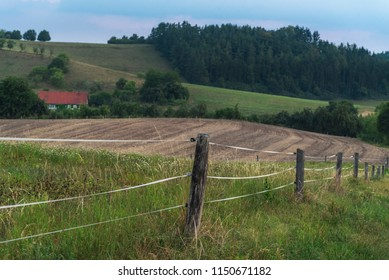 Electrified fence surrounding a farmland with agricultural fields, and a house, in the wooded hills near Schwabisch Hall town, Germany, at dawn.