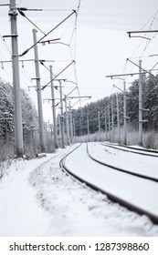 Electrified railway line with poles for wires at winter season, empty road