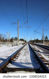 Electrified railway powdered with March snow against a blue sky in the Leningrad region, Russia