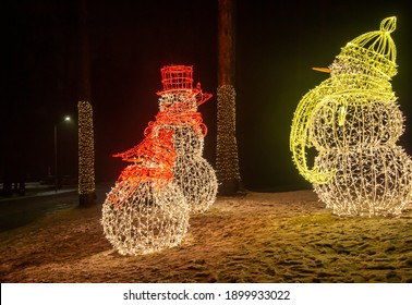 Electrified snowmen with a carrot instead of a nose. The area is full of footprints. Trees with small lights.