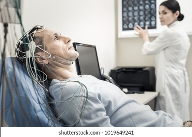 Electro scanning. Nice pleasant handsome man lying on the medical bed and wearing electronic wires while having his brain scanned