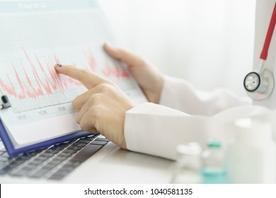 Electrocardiogram, ecg in hand, chart of a doctor. Medical health care. Clinic cardiology heart rhythm and pulse test closeup. Cardiogram printout.