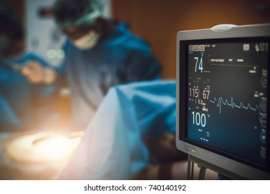 Electrocardiogram in hospital surgery operating  emergency room showing patient heart rate with blur team of surgeons background