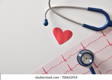 Electrocardiogram stethoscope and paper cutout heart on white table. Top view. Horizontal composition.