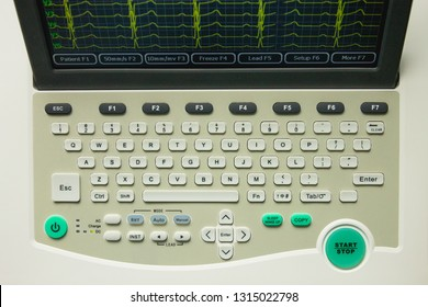 Electrocardiograph medical device with screen and keyboard, top view. Screen showing yellow cardiography heart rythm leads.