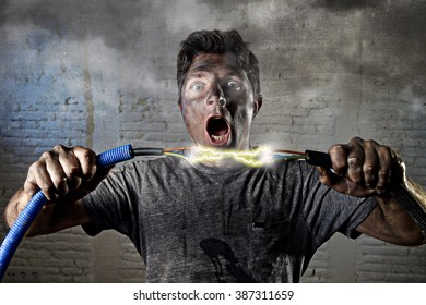 electrocuted man connecting electrical cable smoking having domestic accident with dirty burnt face shock crazy expression in electricity DIY repairs danger concept in black smoke background