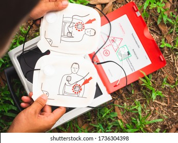 Electrode for attaching to the patient's chest In the hands of people There is a red AED in the back. Placed on the grass. There is a copy space concept, life support equipment, emergency vehicles.