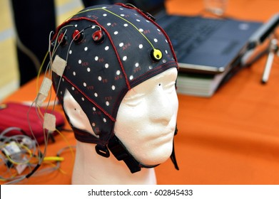 The electroencephalogram (EEG) head cap with flat metal discs (electrodes) attached to a white plastic model's head shown in a science exhibition, with laptops blurred at the background.
