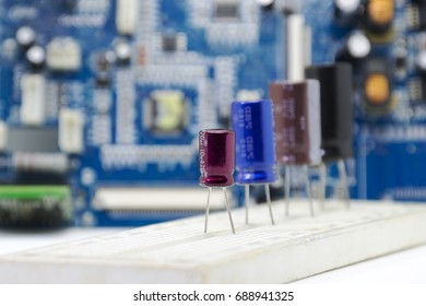 Electrolytic Capacitors, multi color and many sizes an installed in pcb circuit bord and electronics circuit board blurred backdrop, Electronics part concept.