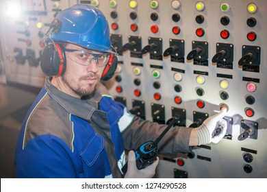 electromechanic in electrical safety gloves holds power cable, cabling connection of high voltage power electric line in industrial distribution fuseboard