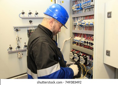 electromechanic in electrical safety gloves holds power cable, cabling connection of high voltage power electric line in industrial distribution fuseboard.