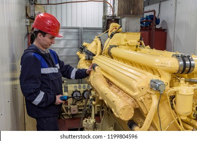 Electromechanic performs repair work on a diesel generator