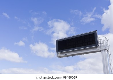 Electronic advertising panel against a background of blue sky with clouds.