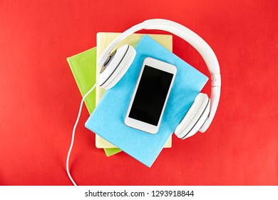 Electronic audiobook vs regular paper book concept. Stack of different color hardcover books with blank colorful covers & white headphones on table. Old versus new. Close up, copy space, background.