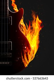 Electronic bass guitar enveloped flames on a black background.