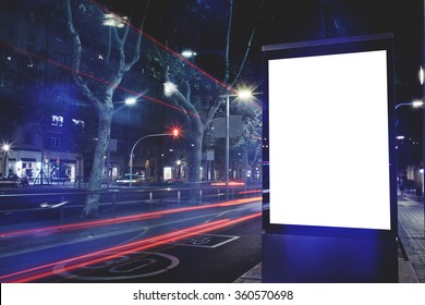 Electronic blank billboard with copy space for your text message or content, public information board with cars lights on background, advertising mock up in urban setting, empty poster on roadside
