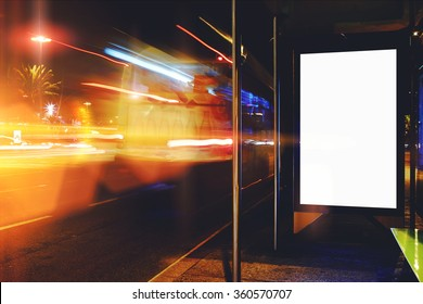 Electronic blank billboard with copy space for your text message or promotional content, clear public information board in night city with cars's movement on background, bus stop advertising mock up