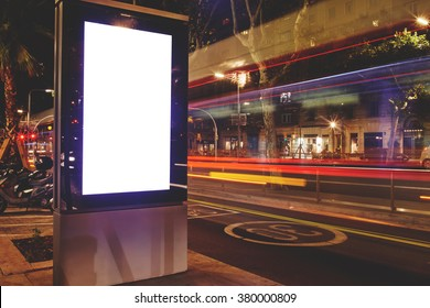 Electronic blank billboard with copy space for your text message or content, public information board in night city with blurred movement of cars on background, advertising mock up banner on roadside