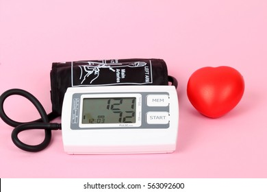 electronic blood pressure meter on pink ground