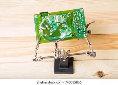 Electronic board in a clip under Magnifying Glass (focus on a glass)