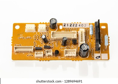 Electronic board with electrical parts in a collection on a white background. The board has microcircuits, transistors, diodes, capacitors, resistors and sockets.