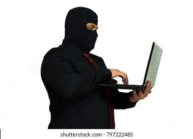Electronic burglar in the balaclava. In the hands of a laptop. computer crime