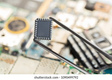 electronic chip in tweezers on background of the disassembled mobile phone