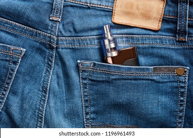 Electronic cigarette in the back pocket of a blue jean. Concept of vaping youth.