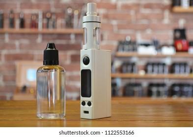 Electronic cigarette with ejuice bottle on a background of vape shop. E-cigarette for vaping. Popular vape devices
