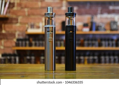 Electronic cigarette on a background of vape shop. E-cigarette for vaping. Popular vape devices