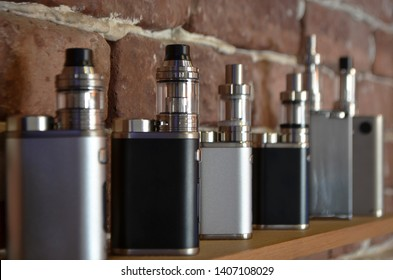 Electronic cigarette on a background of vape shop. E-cigarette for vaping. Popular vape devices