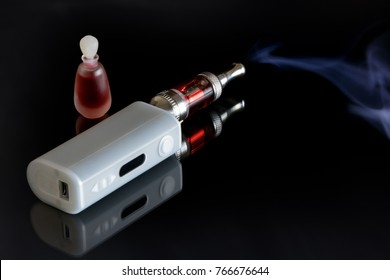 An Electronic cigarette (or e-cigarette) emitting vapor and a small bottle full of red e-liquid on dark background.