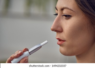 Electronic Cigarette Technology. Tobacco IQOS system. Close-up of a girl smoking an electric hybrid cigarette with a heating pad. tobacco heating system. Electronic cigarette in female hands.