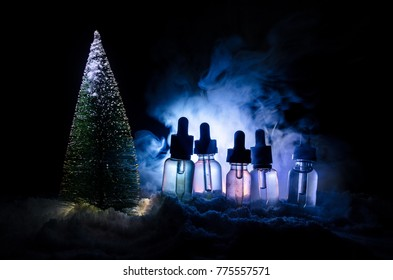 Electronic cigarette with vape liquids and christmas decorations on bokeh lights background with New Year atributes or symbols. Selective focus