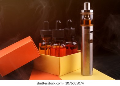 Electronic cigarette and vape liquids into opened gift box on fogged dark background. Toned light