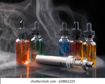 Electronic cigarette and vape liquids within vapor on black background