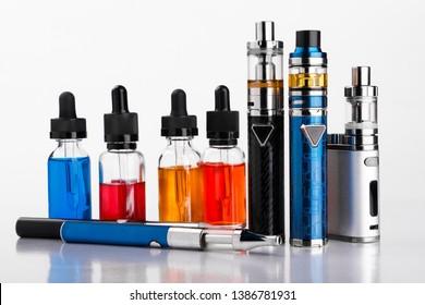 Electronic cigarettes and bottles with vape liquid on white background
