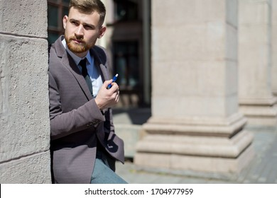 electronic cigarettes iqos. Portrait of a young bearded guy of twenty-five years old, stands by the textured wall of the building, smokes a cigarette. Outdoor