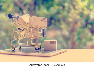 Electronic commerce or eCommerce and online shopping concept : Goods, boxes in a shopping cart on a white smart tablet, depicts consumer shopping experience via immersive detail before making decision